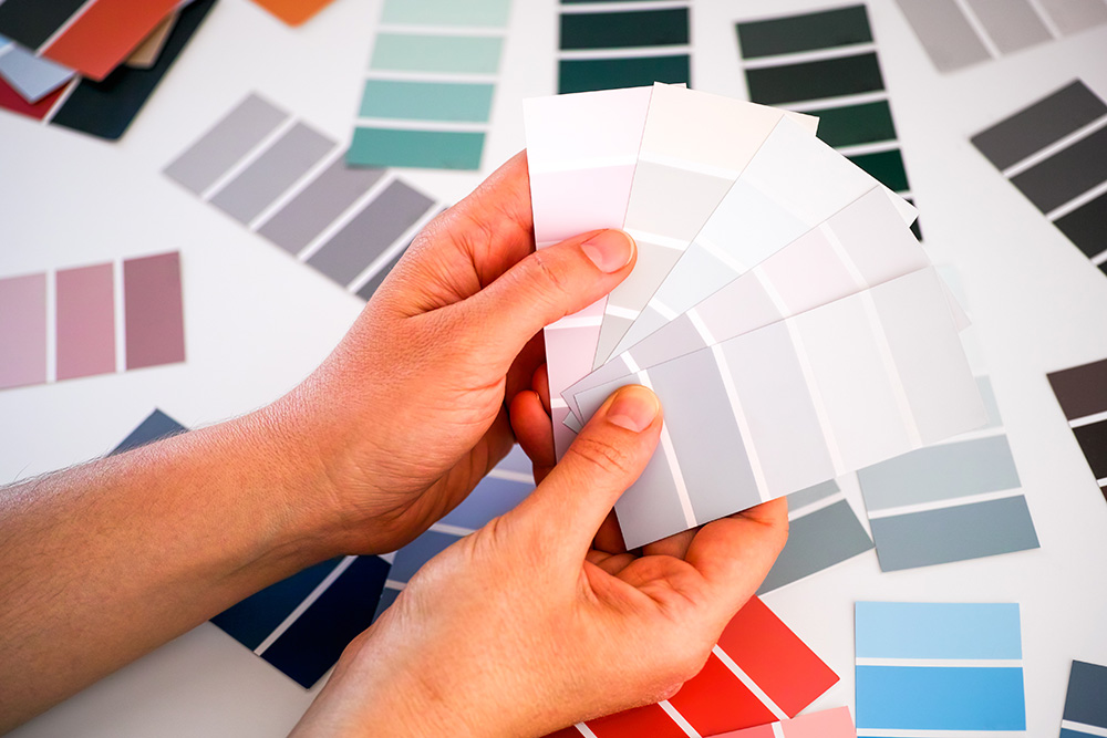 Woman hands choosing colour in color swatches. Closeup.